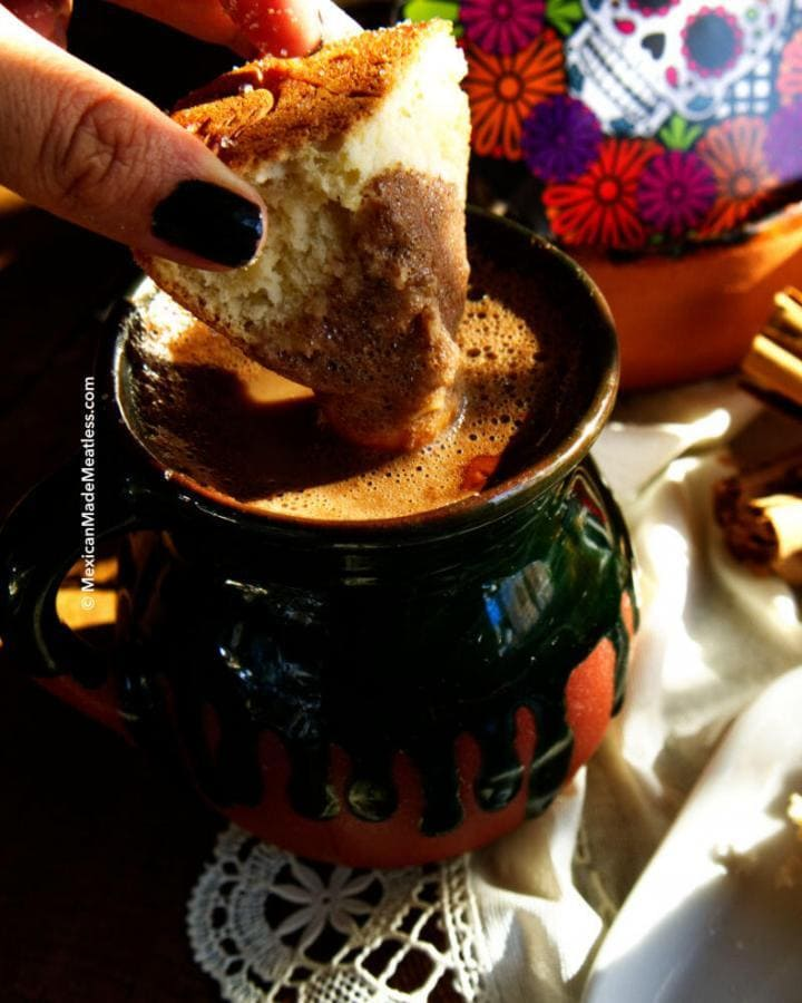 Pan dulce being dipped into a cup of hot chocolate