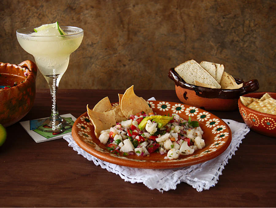 A plate of vegan cauliflower ceviche served with corn chips and an ice-cold classic margarita.