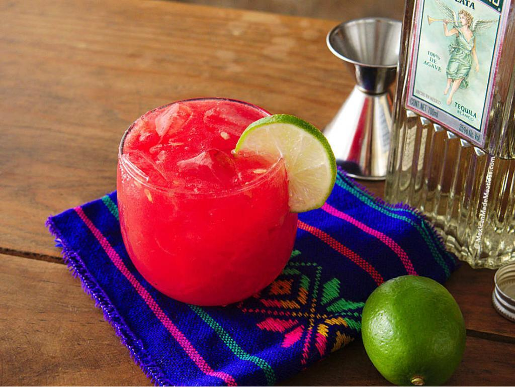 A watermelon and blanco tequila cocktail with a slice of lime.